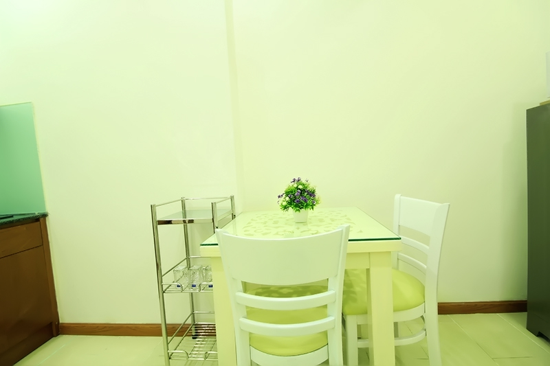 1751-0604 A white wooden dining table is located in the kitchen of serviced apartment in District 1